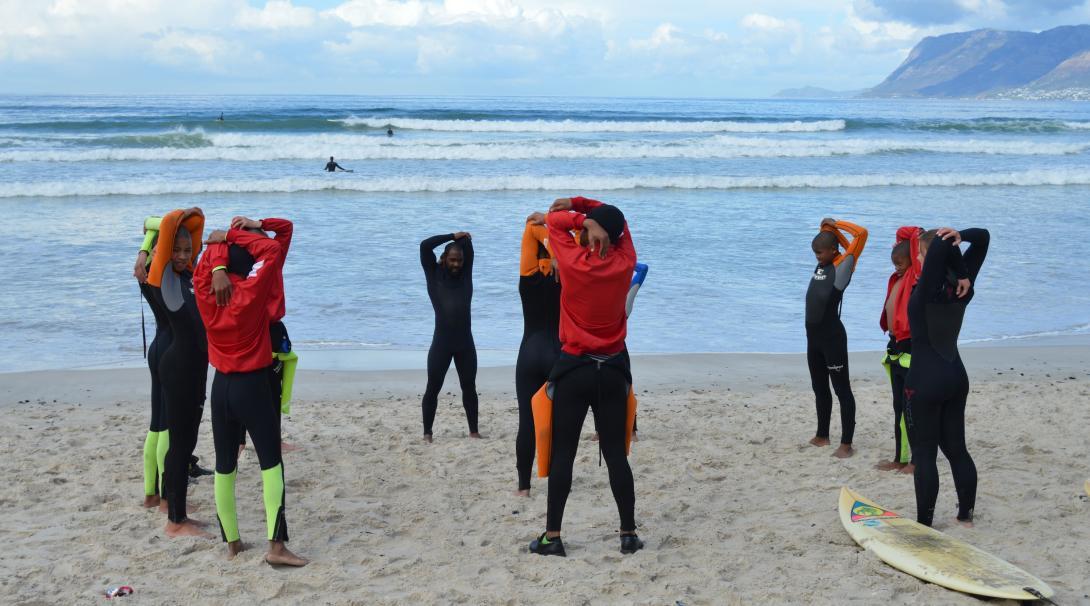 L'entraîneur de surf Projects Abroad mène une série d'échauffement sur la plage.